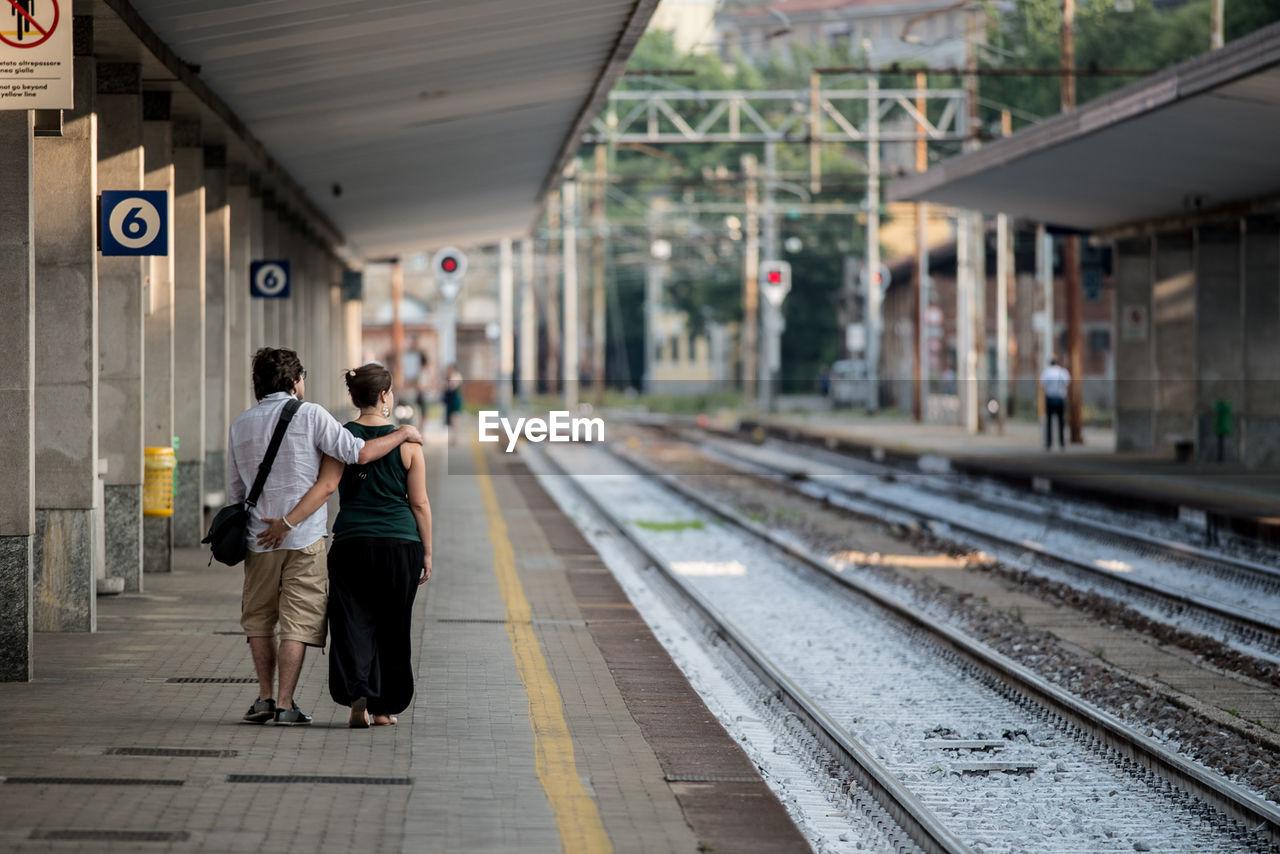 Rear View Of Couple Walking At Railroad Station Platform
