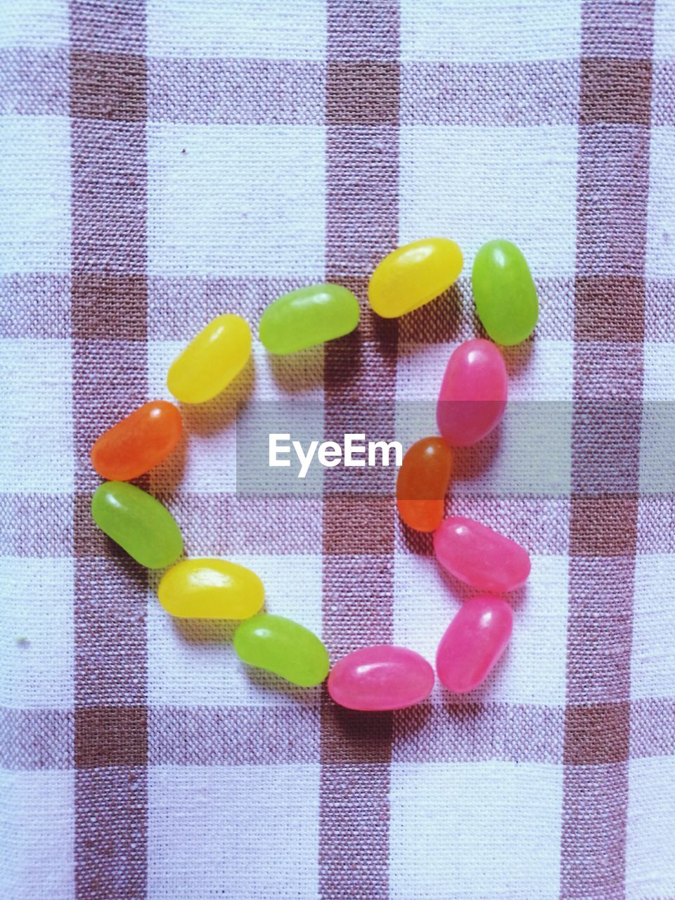 Directly above shot of candies arranged as heart shape on table