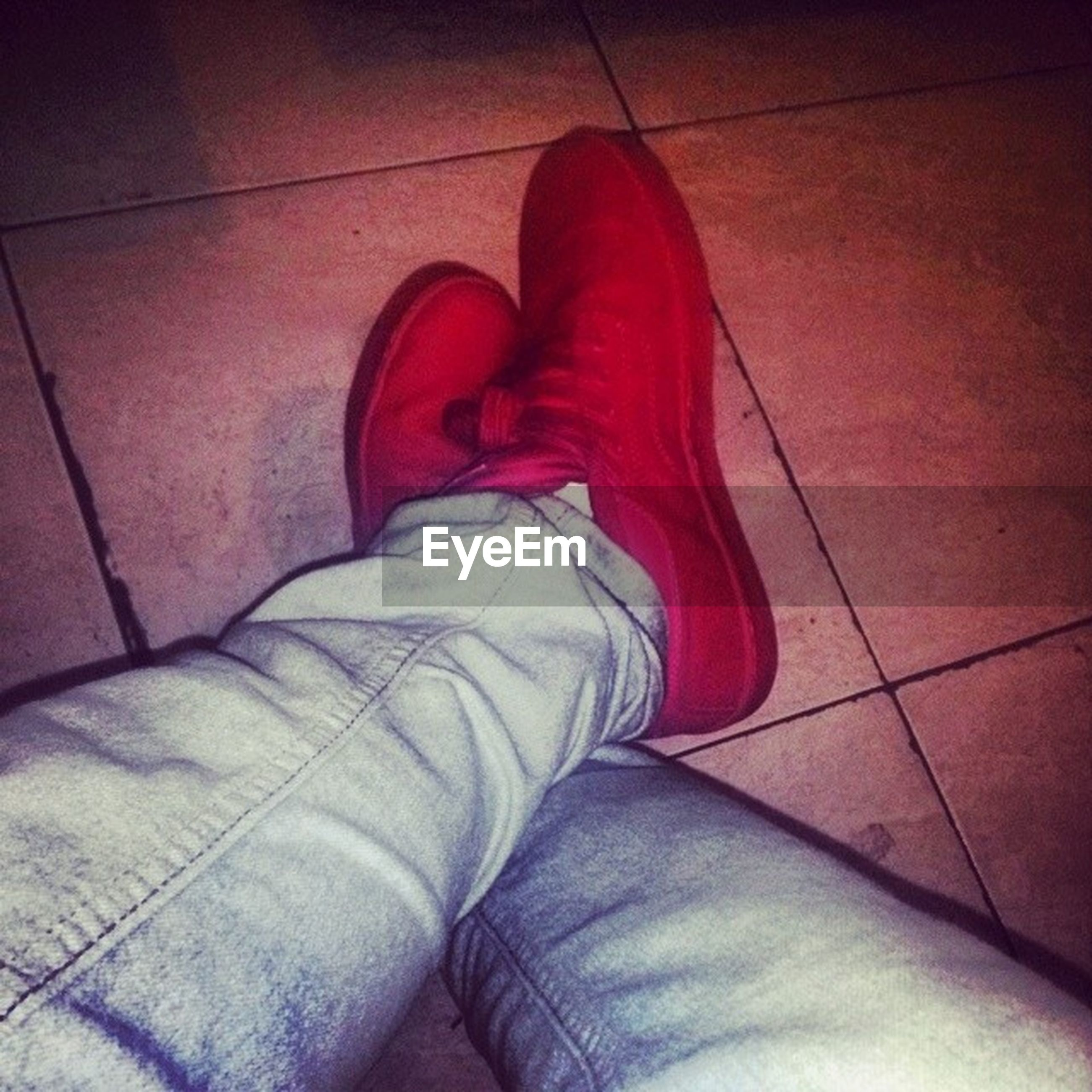 low section, person, shoe, indoors, jeans, footwear, high angle view, red, personal perspective, human foot, relaxation, standing, tiled floor, flooring, canvas shoe, sock, lifestyles