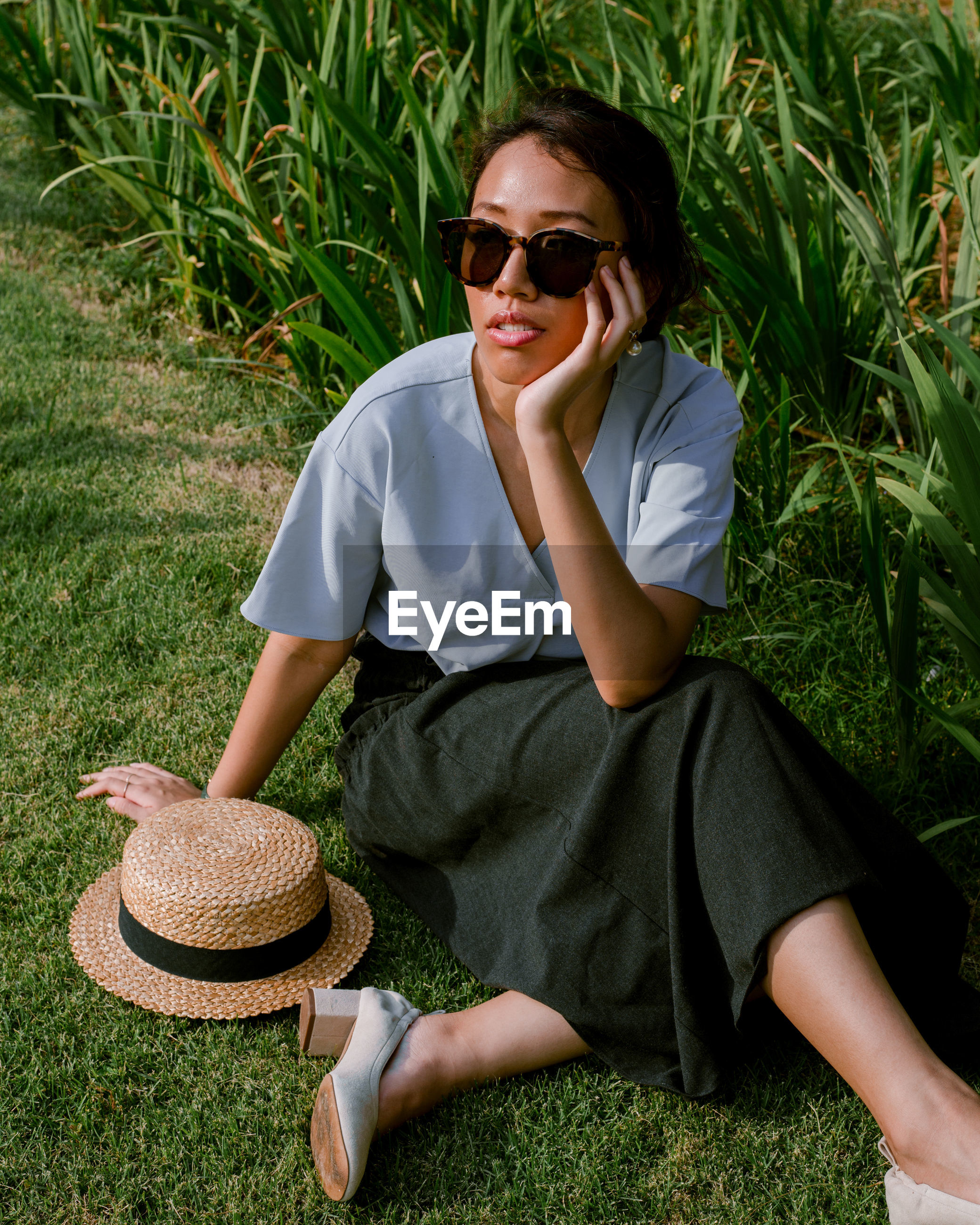 real people, leisure activity, sunglasses, glasses, grass, one person, plant, casual clothing, lifestyles, fashion, young adult, hat, sitting, nature, full length, day, front view, young women, outdoors