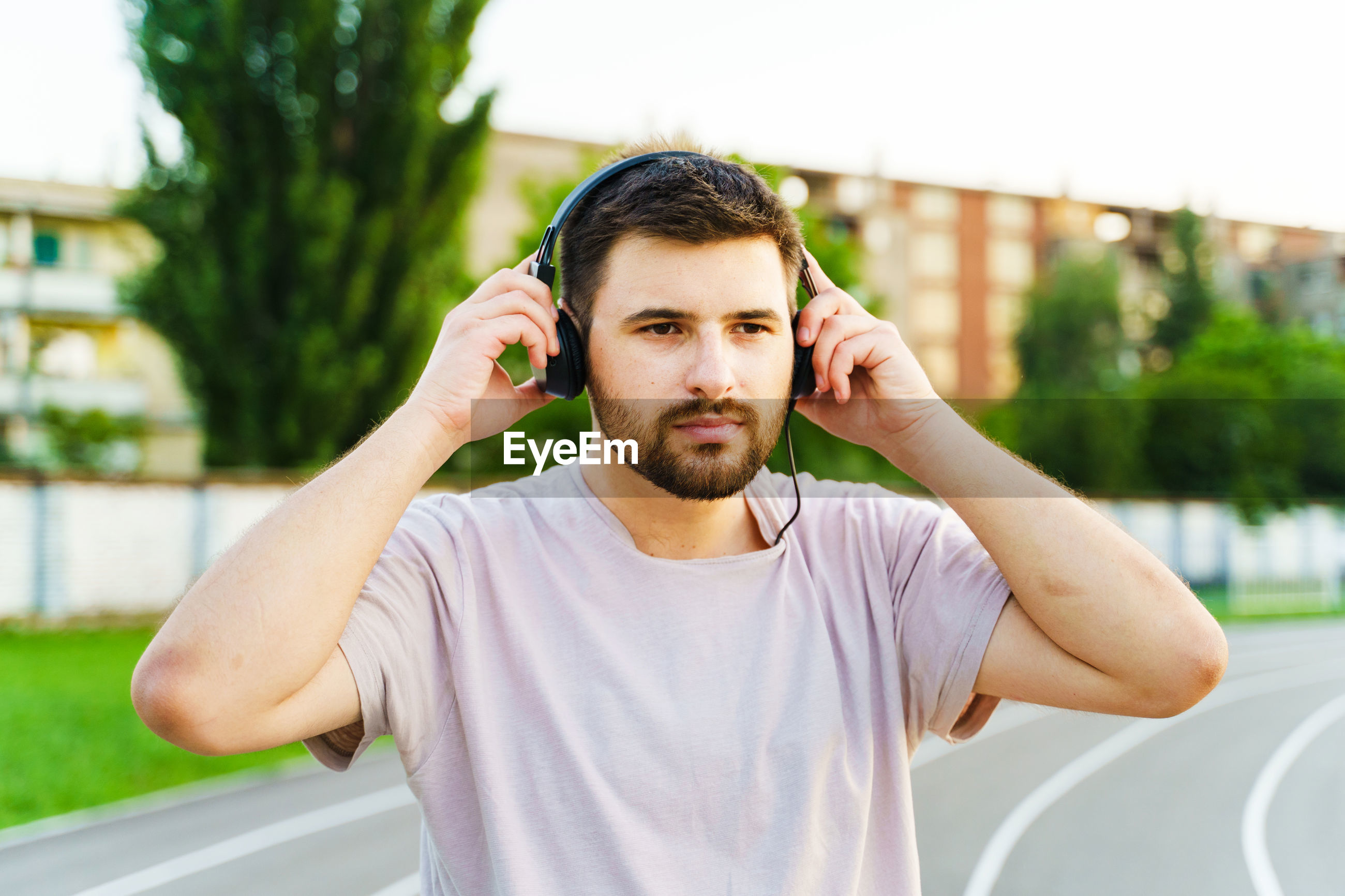 Man listening music over headphones while standing outdoors