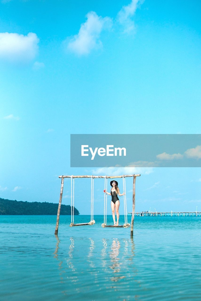 Woman Standing On Swing Over Sea Against Blue Sky