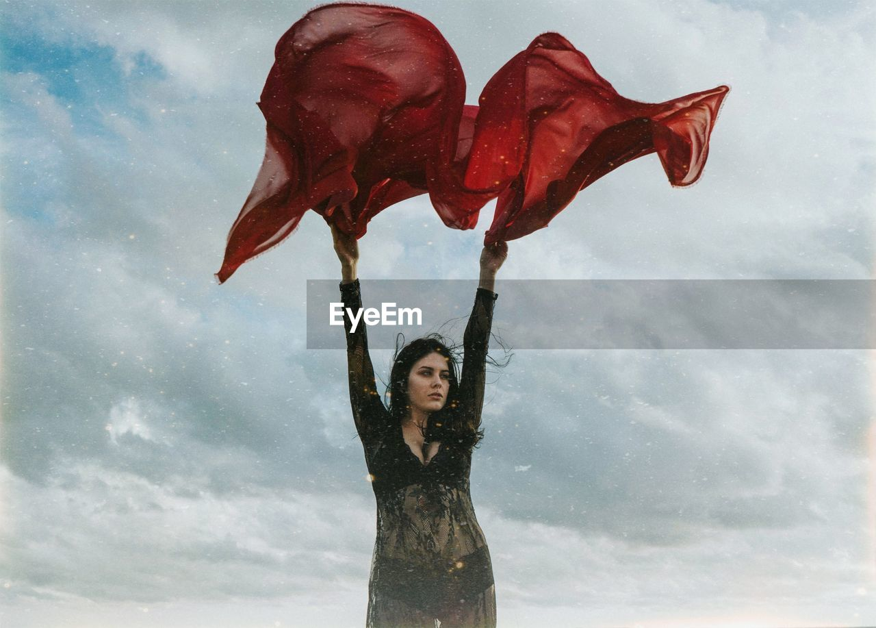 Young woman holding red textile while standing against cloudy sky