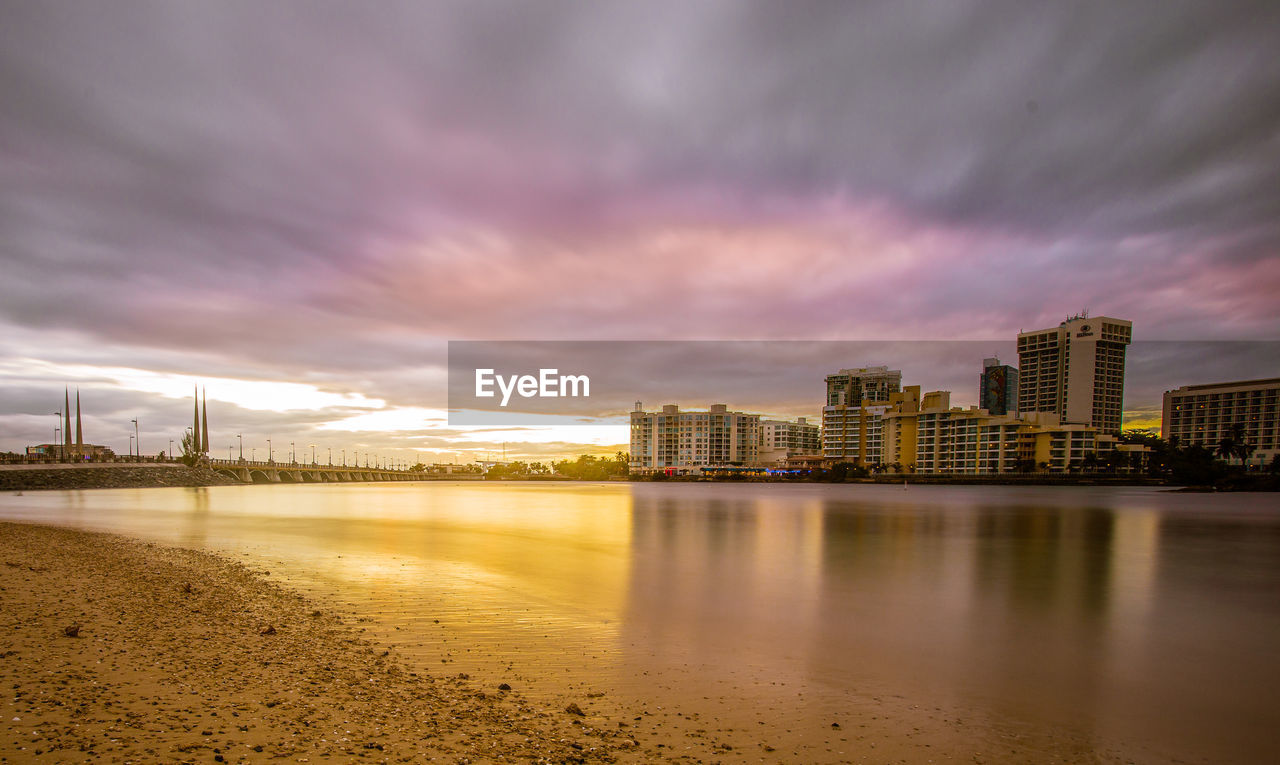 architecture, sky, built structure, cloud - sky, building exterior, water, city, reflection, no people, sunset, outdoors, skyscraper, cityscape, nature, sea, day