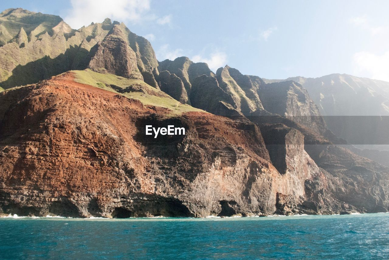 mountain, sky, water, sea, nature, rock, scenery, beauty in nature, scenics - nature, environment, no people, landscape, outdoors, waterfront, day, wilderness, sunlight, horizon, rock - object, mountain peak, formation, height, high, mountain range, view into land, eroded, range