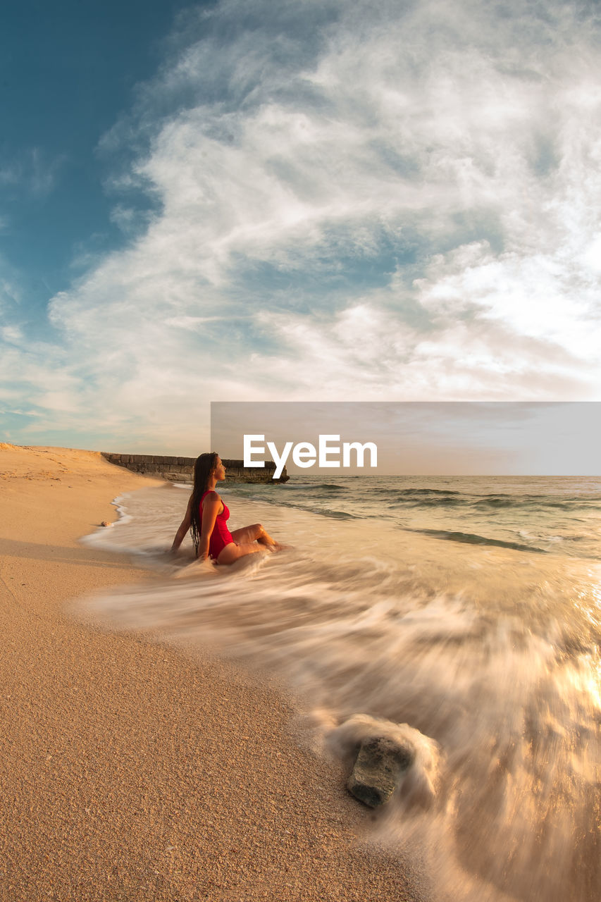 sky, land, cloud - sky, one person, real people, beauty in nature, sand, lifestyles, scenics - nature, nature, women, beach, leisure activity, tranquil scene, water, non-urban scene, tranquility, idyllic, adult, outdoors, climate, arid climate