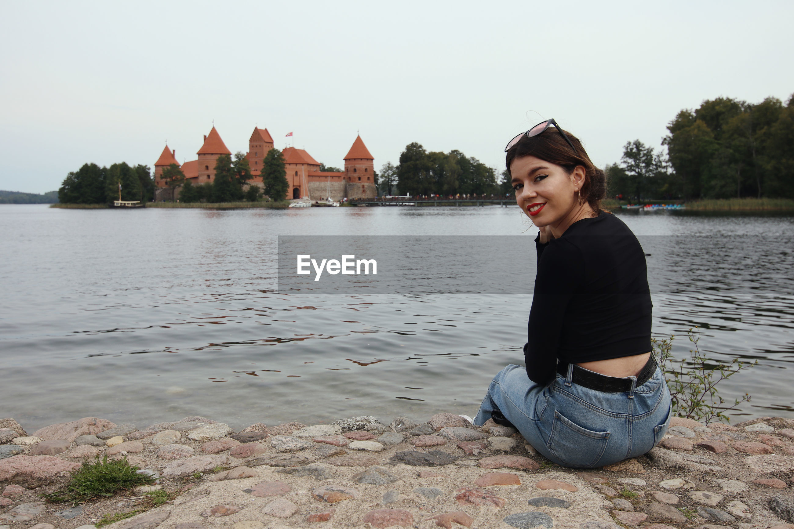 Portrait of young woman sitting by lake against sky