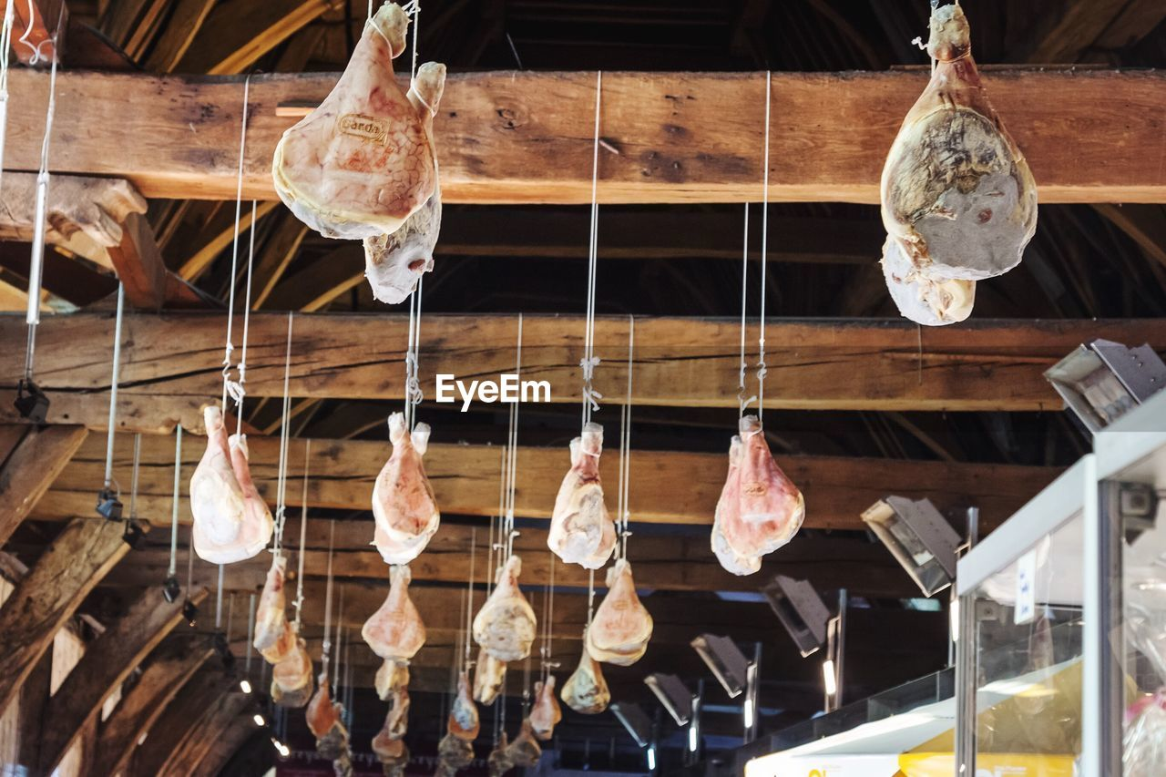 Low Angle View Of Meats Hanging From Ceiling At Butcher Shop