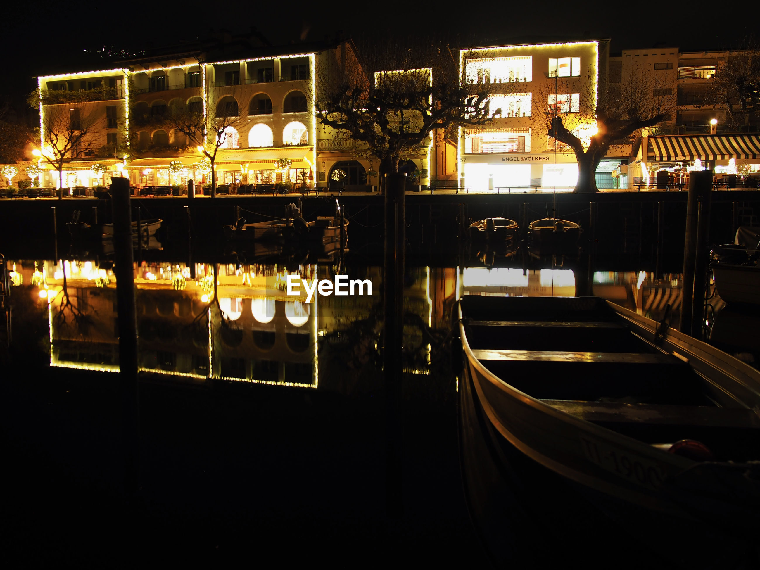 VIEW OF BOATS MOORED IN ILLUMINATED CITY AT NIGHT