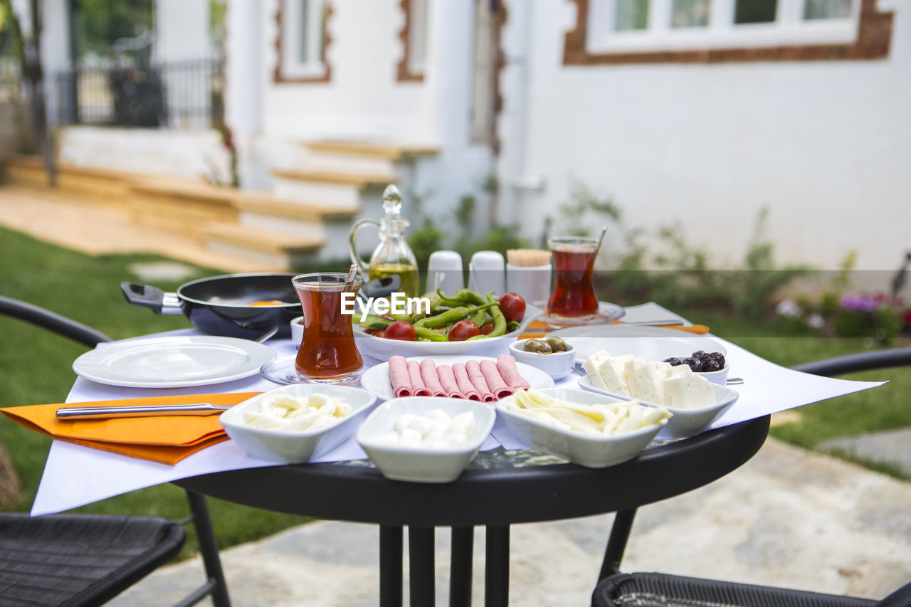 table, food and drink, food, freshness, focus on foreground, plate, no people, seat, glass, ready-to-eat, chair, place setting, drink, restaurant, healthy eating, drinking glass, household equipment, day, vegetable, meal, setting, outdoors, crockery, breakfast