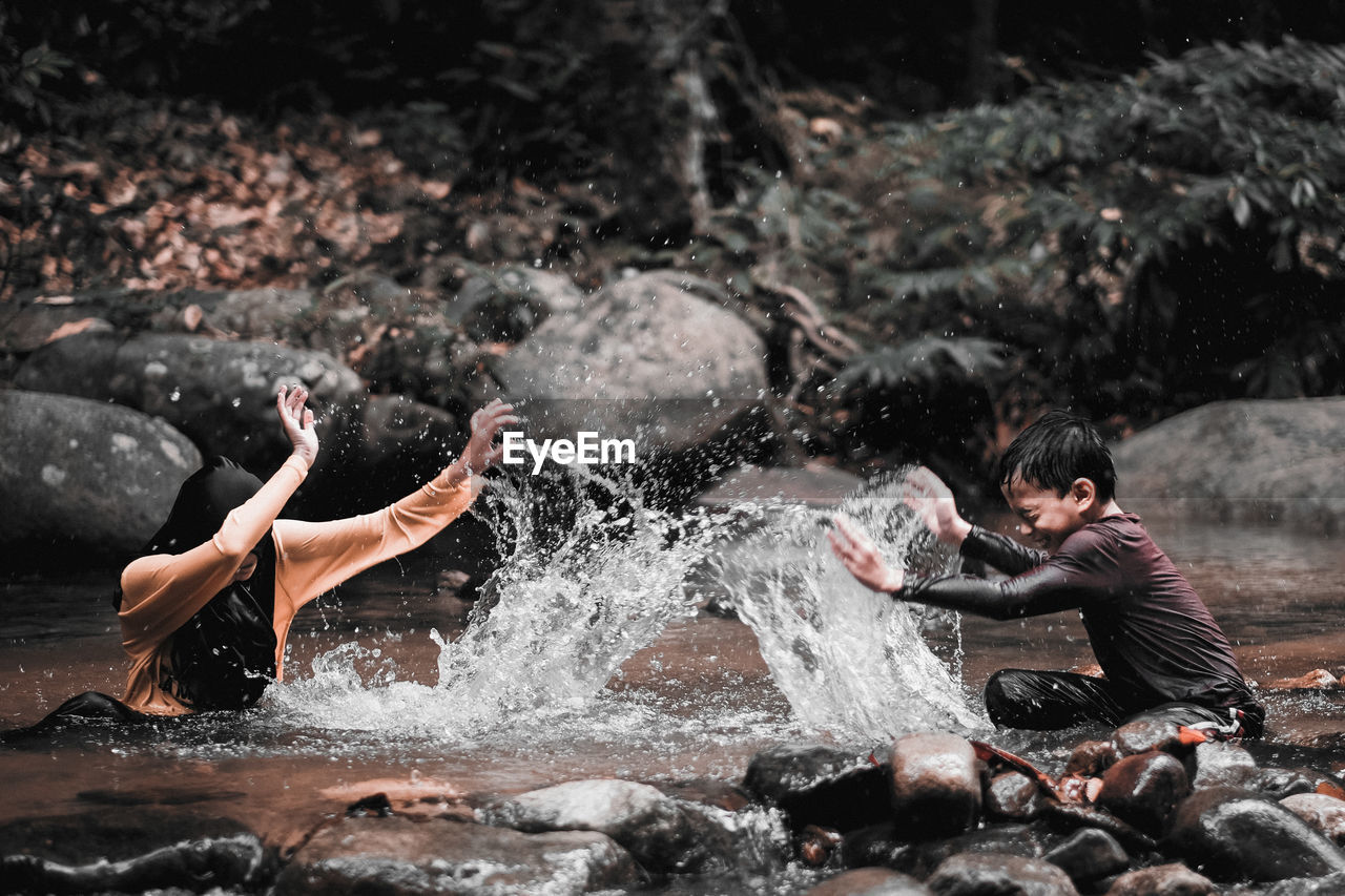 motion, splashing, water, real people, nature, lifestyles, two people, men, enjoyment, leisure activity, males, day, shirtless, people, togetherness, waterfront, outdoors, young adult, side view