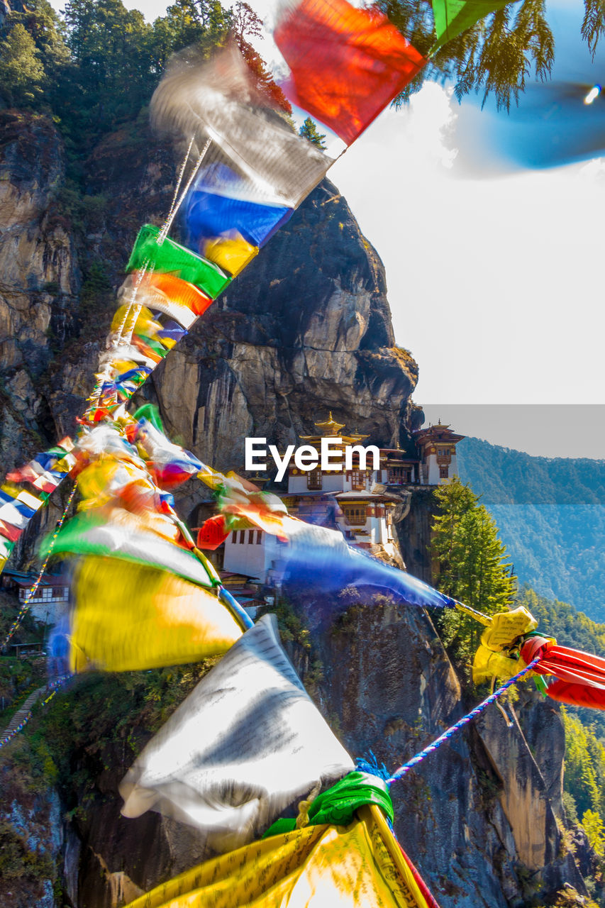 Buddhist Temples On Cliff Against Mountains With Prayer Flags