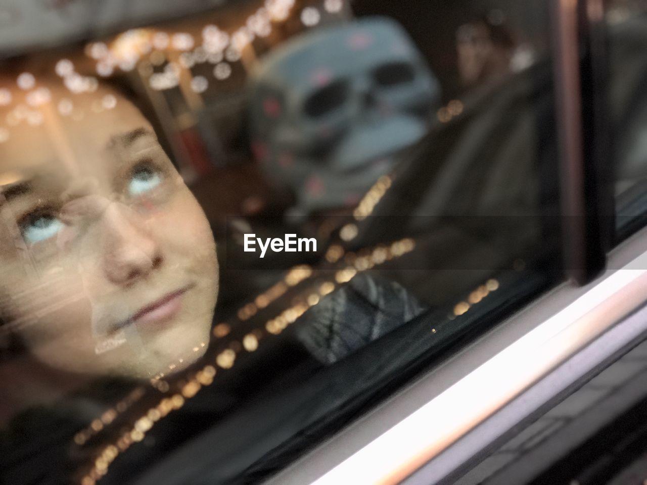 CLOSE-UP PORTRAIT OF MAN SEEN THROUGH CAR WINDOW
