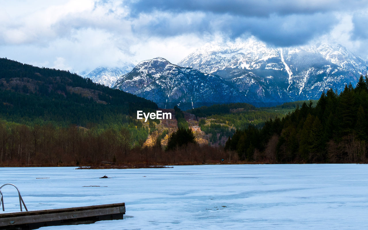 mountain, snow, nature, beauty in nature, scenics, winter, cold temperature, mountain range, tranquility, weather, tranquil scene, outdoors, day, tree, sky, no people, lake, snowcapped mountain, water, landscape
