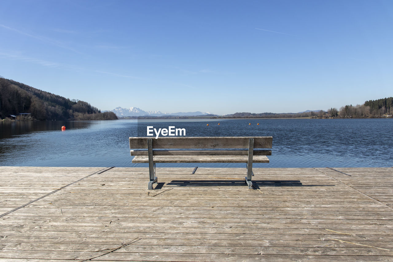EMPTY BENCH IN LAKE AGAINST SKY