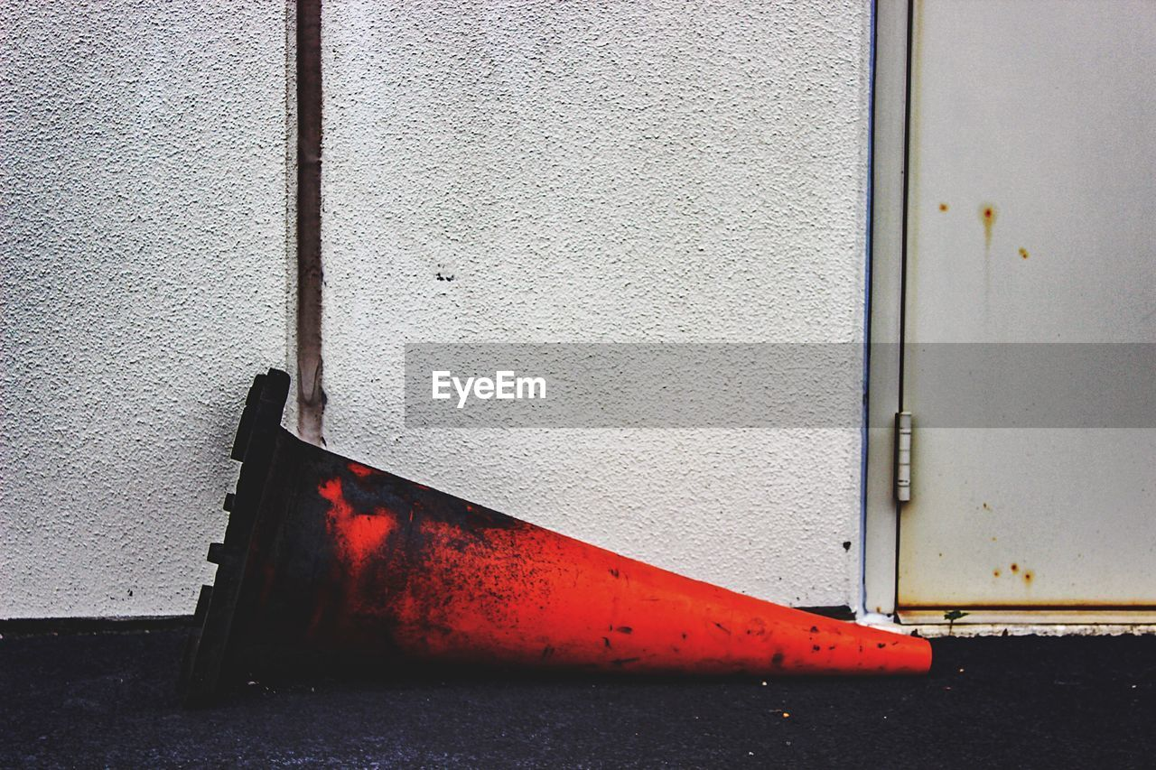 Burnt traffic cone against white wall