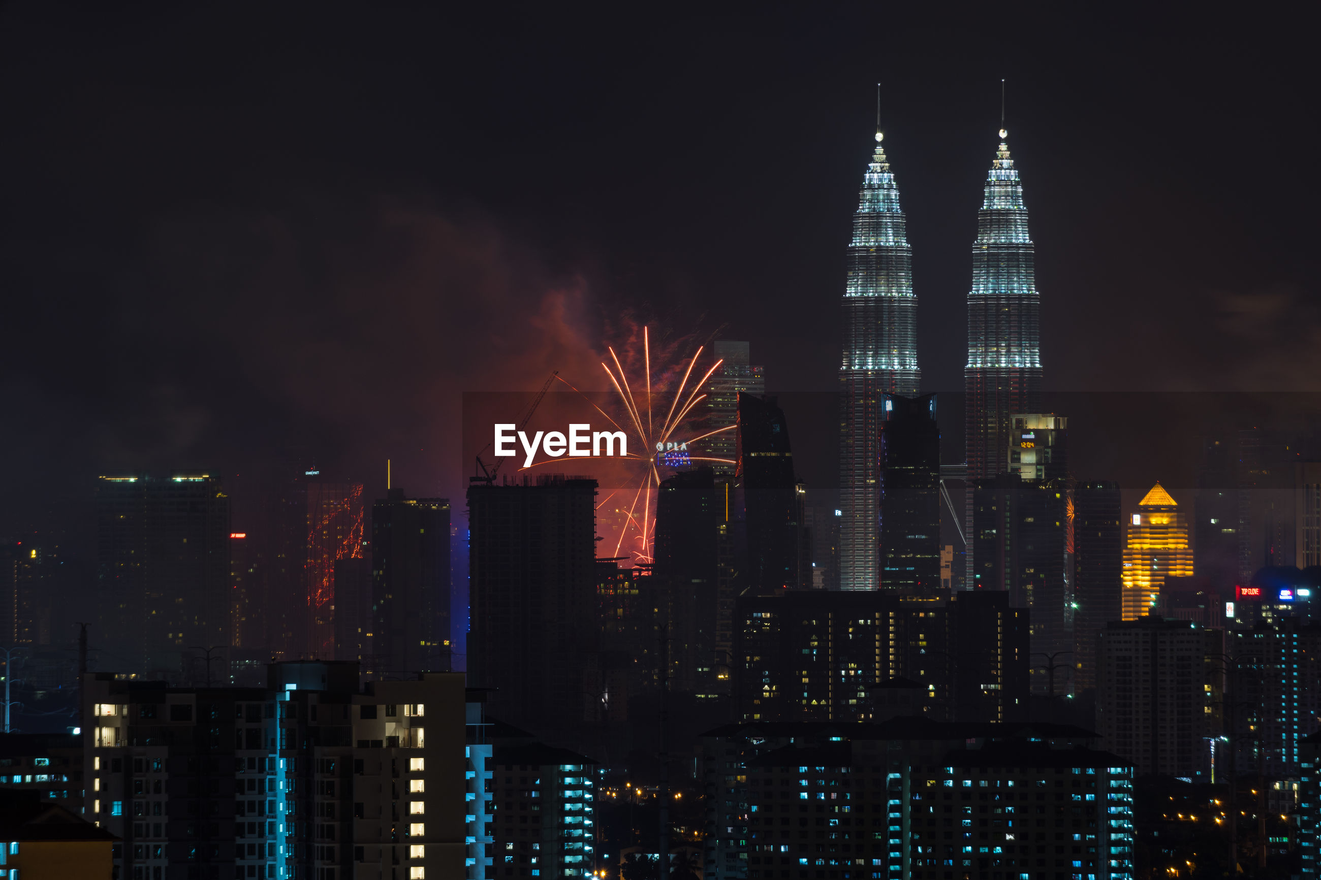 Illuminated petronas towers and fireworks at night