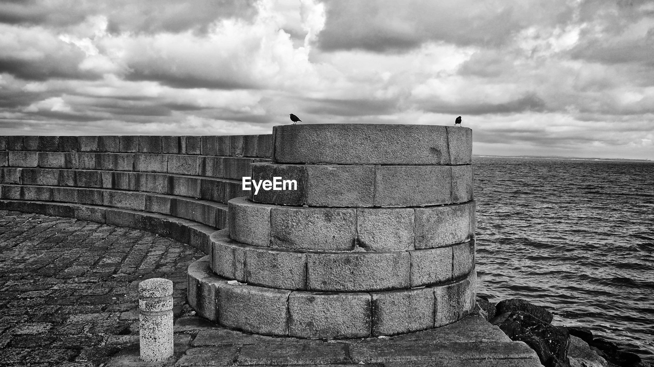 Retaining wall by sea against cloudy sky
