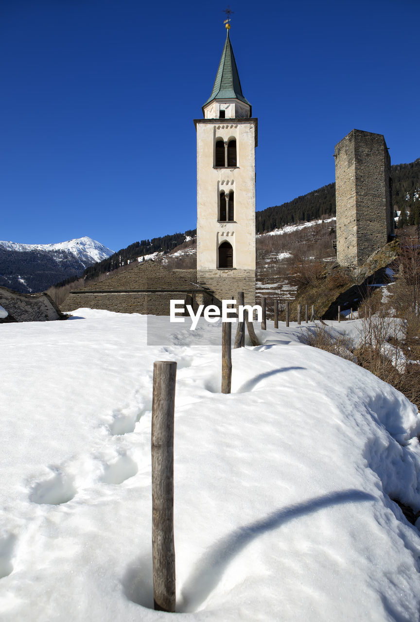 snow, winter, cold temperature, built structure, architecture, sky, nature, religion, building, building exterior, belief, place of worship, spirituality, day, mountain, tower, no people, outdoors, snowcapped mountain