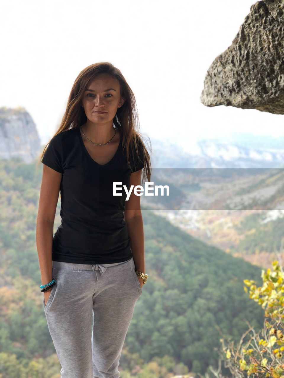 Portrait of young woman standing on mountain against sky