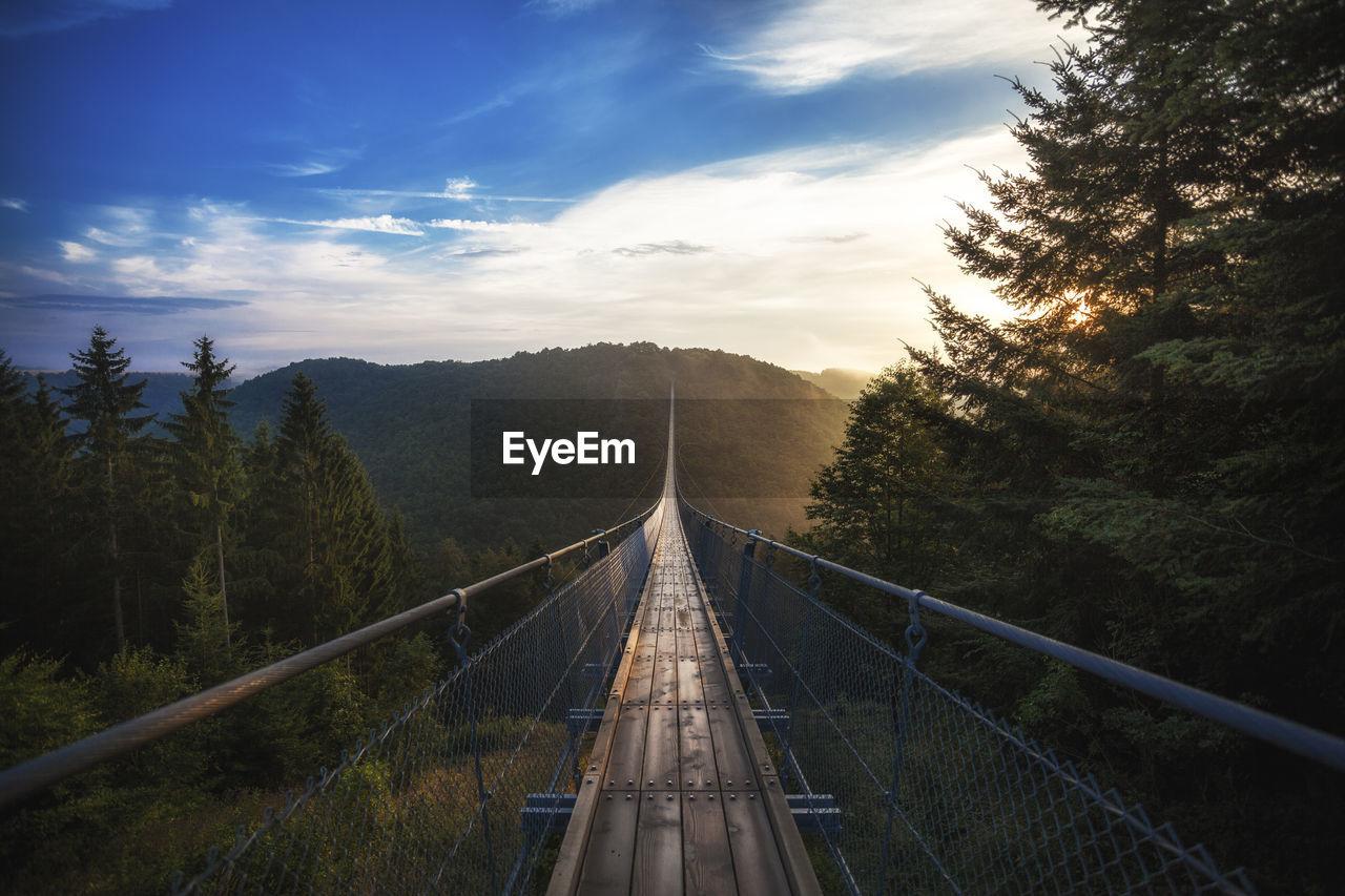 Empty Suspension Footbridge Over Mountains Against Sky