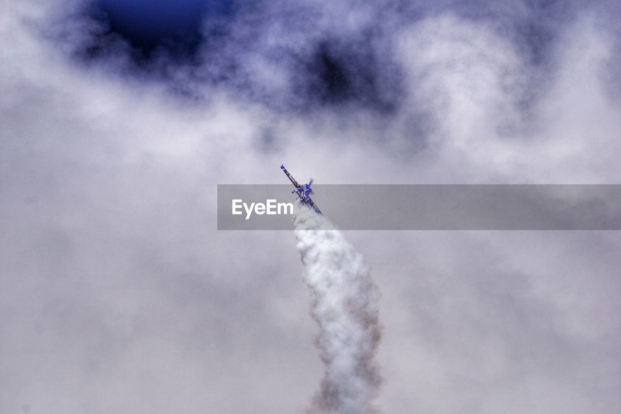 Low Angle View Of Airplane Flying In Cloudy Sky During Airshow