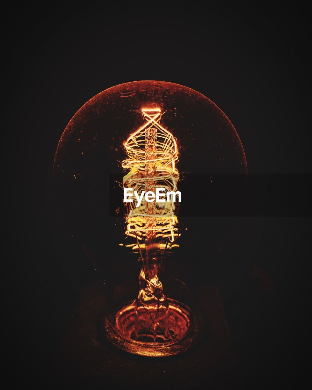 illuminated, light bulb, electricity, lighting equipment, filament, indoors, black background, light, no people, studio shot, glass - material, glowing, close-up, transparent, dark, electric light, light - natural phenomenon, single object, orange color, technology, power supply, electrical equipment