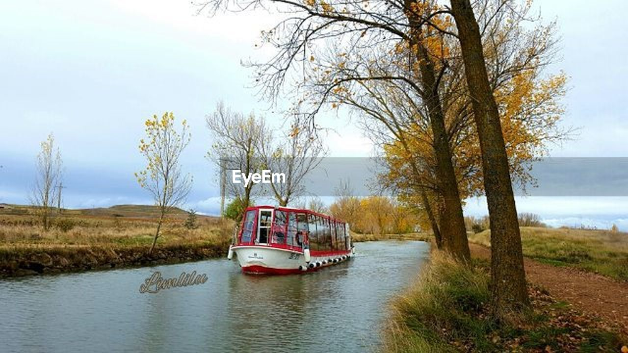 transportation, river, tree, sky, water, mode of transport, outdoors, travel, cloud - sky, day, journey, bare tree, grass, nature, rural scene, nautical vessel, no people