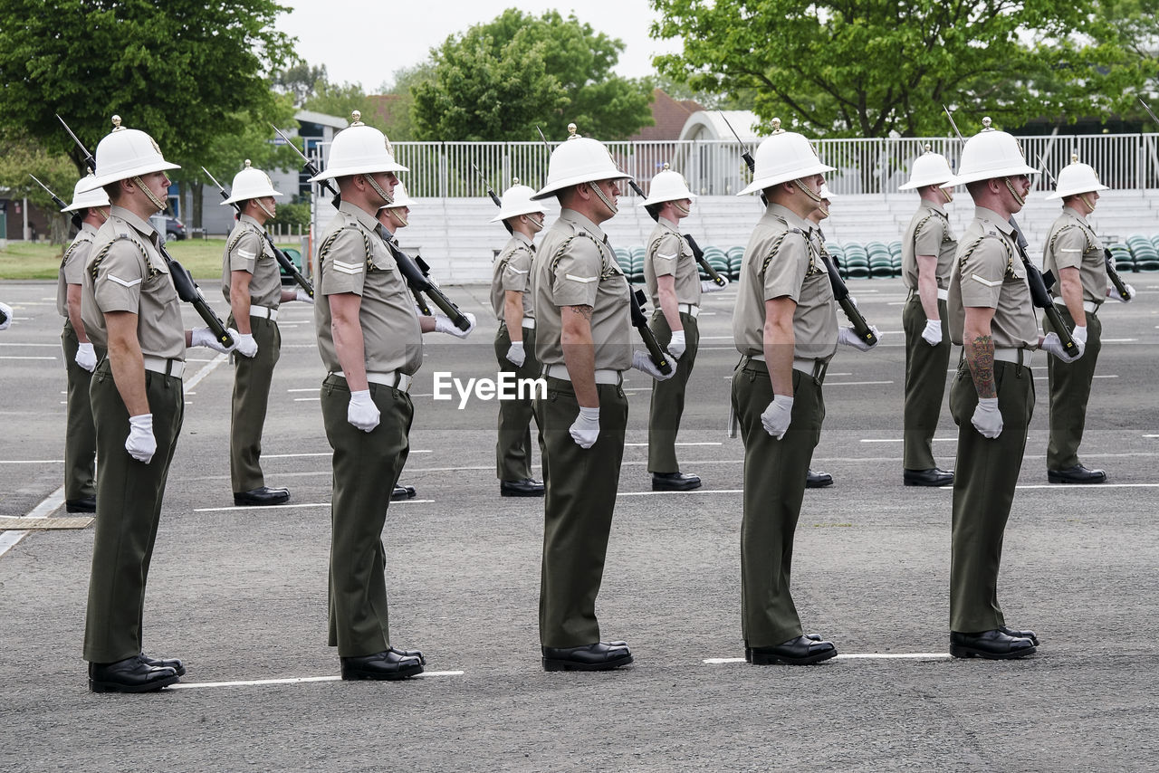 uniform, government, clothing, group of people, full length, armed forces, military, weapon, army soldier, real people, day, security, protection, people, military uniform, standing, safety, men, side by side, outdoors, marching band