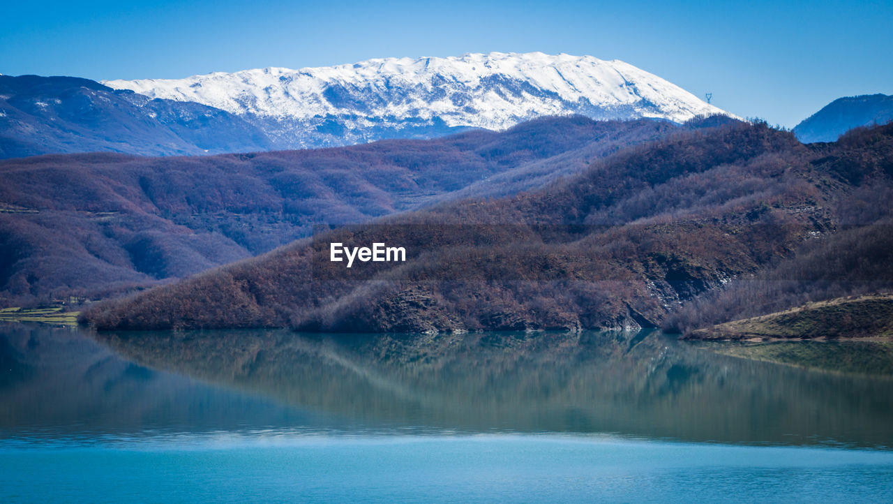 mountain, water, beauty in nature, mountain range, scenics - nature, lake, sky, tranquil scene, nature, tranquility, waterfront, environment, no people, landscape, cold temperature, reflection, day, non-urban scene, outdoors, snowcapped mountain, mountain peak, turquoise colored, range