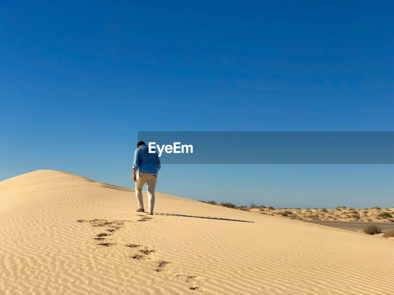 Rear view of man walking on sand in desert against sky