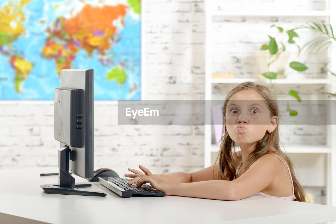Portrait of girl puckering while using computer at table