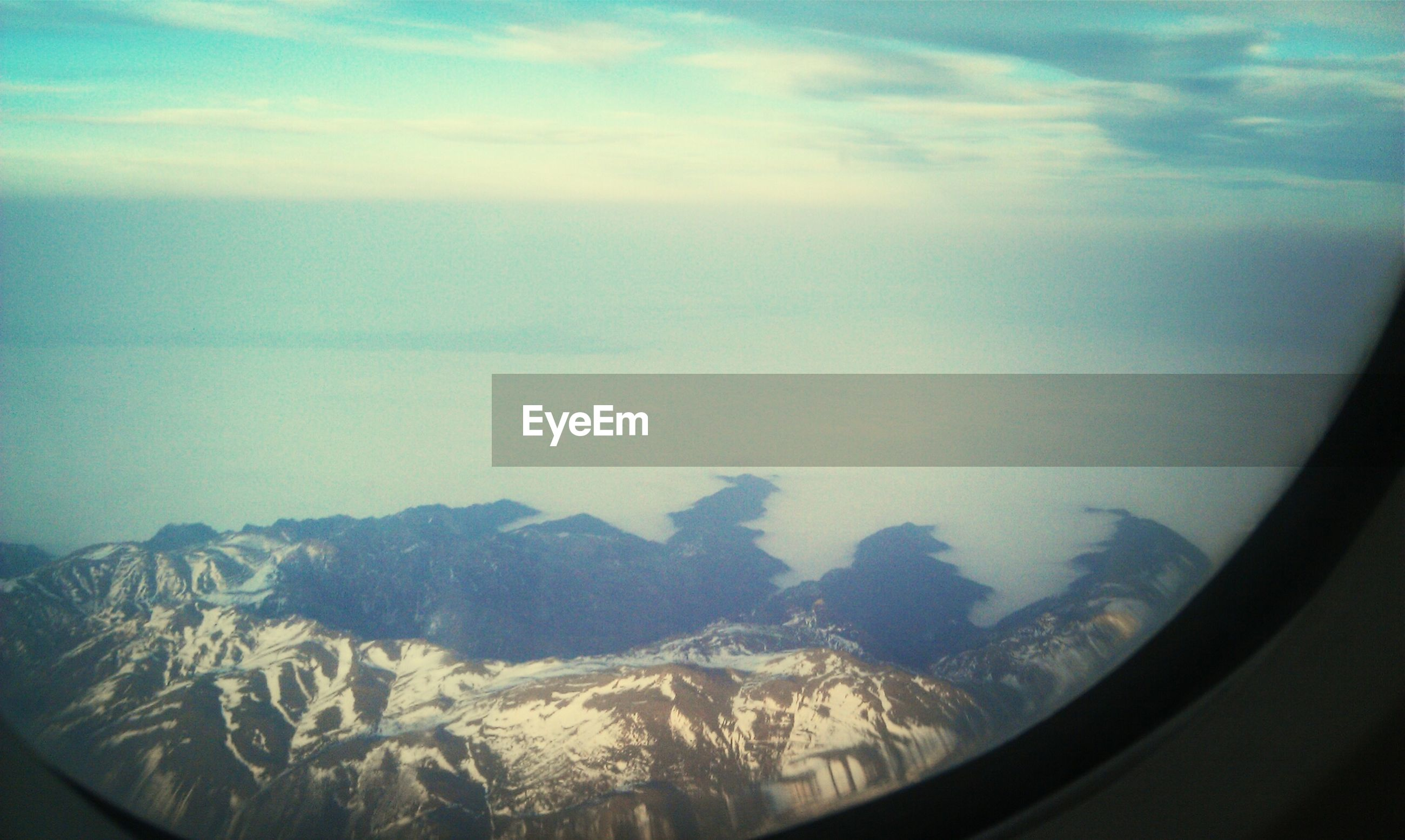 aerial view, airplane, scenics, air vehicle, landscape, mountain, snow, sky, beauty in nature, window, winter, cold temperature, tranquil scene, nature, cloud - sky, vehicle interior, aircraft wing, tranquility, transportation, mountain range