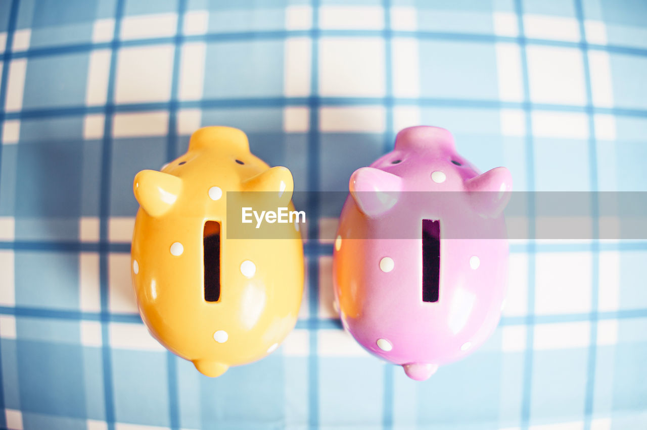 piggy bank, indoors, no people, focus on foreground, close-up, investment, pink color, representation, finance, savings, animal representation, still life, business, yellow, toy, side by side, rubber duck, two objects, group of objects, coin bank, consumerism