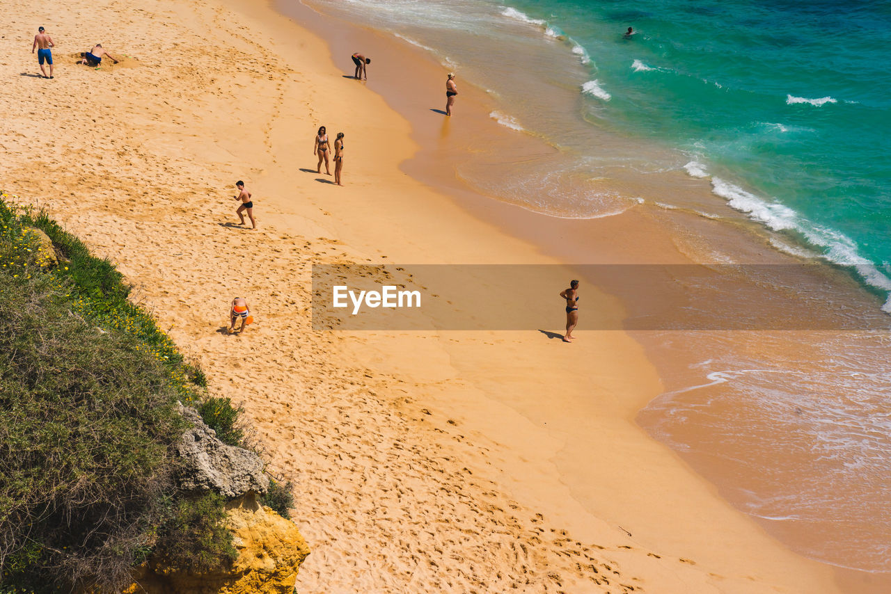 land, sea, beach, water, real people, sand, high angle view, holiday, group of people, vacations, trip, nature, lifestyles, leisure activity, day, sport, people, incidental people, men, outdoors