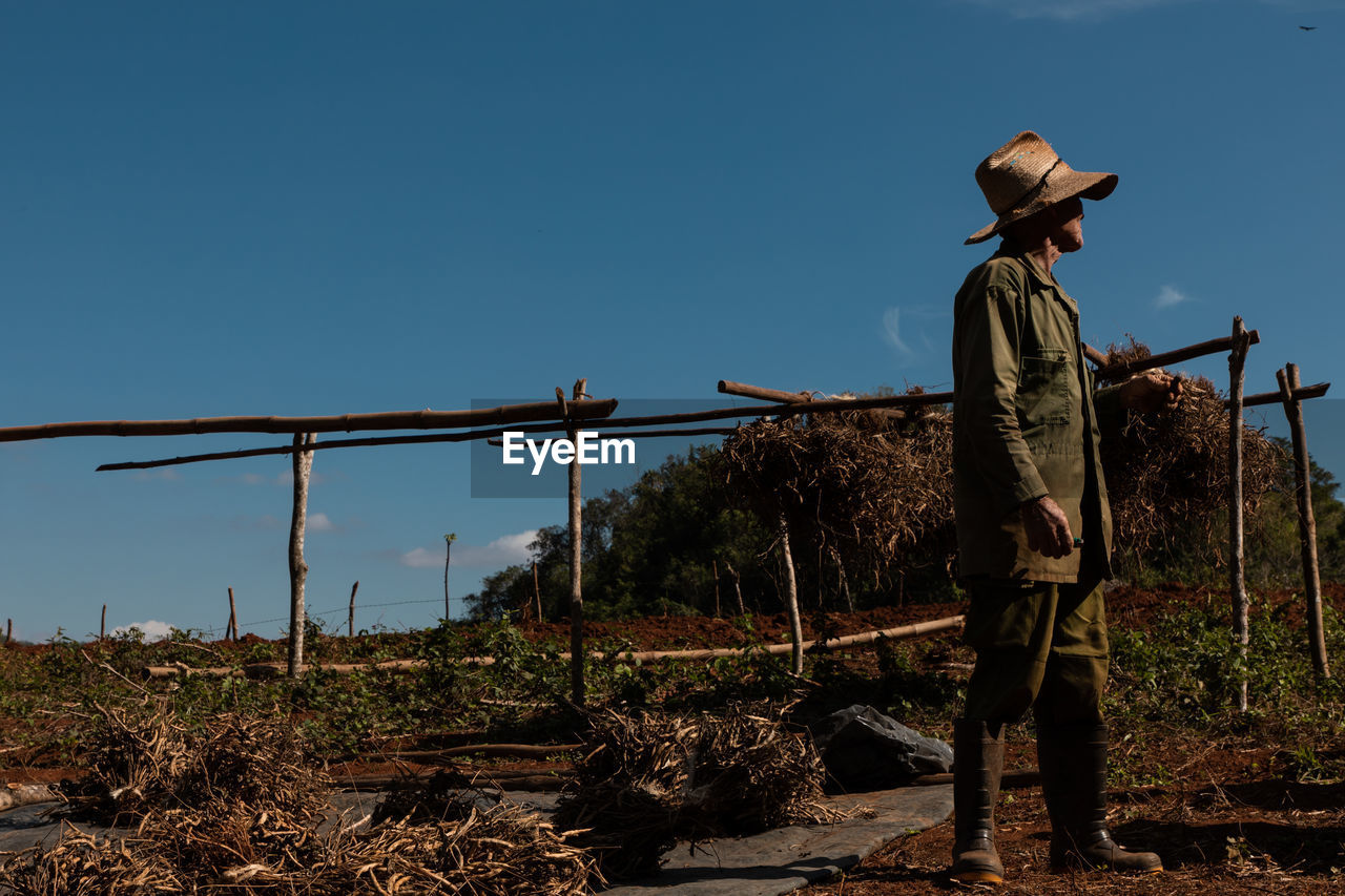 sky, nature, real people, land, full length, field, hat, standing, occupation, day, clear sky, clothing, men, landscape, people, plant, working, rear view, lifestyles, farmer