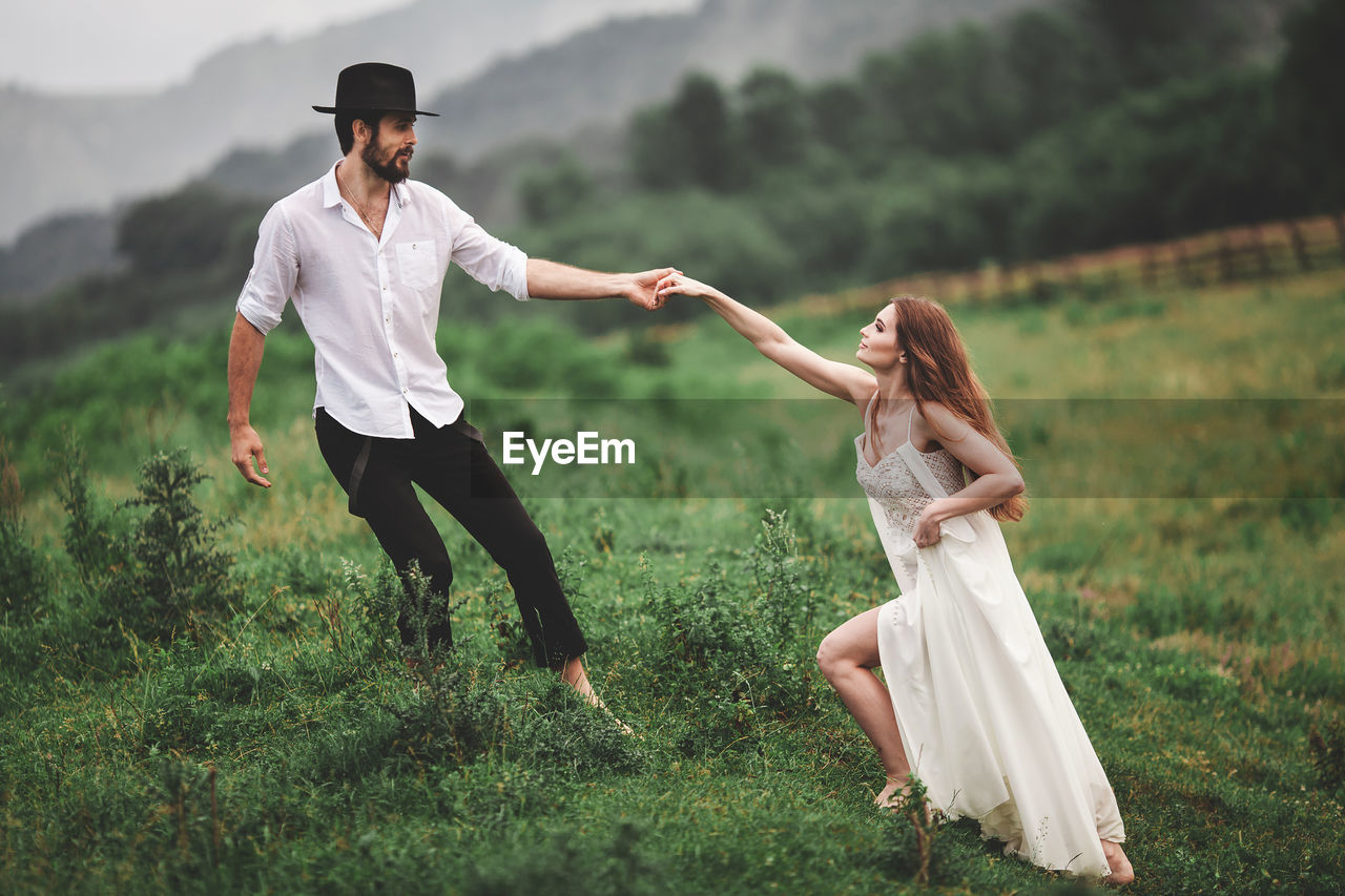 two people, real people, young adult, land, leisure activity, full length, field, grass, togetherness, lifestyles, plant, nature, bonding, women, casual clothing, people, emotion, young women, day, couple - relationship, positive emotion, outdoors, hairstyle
