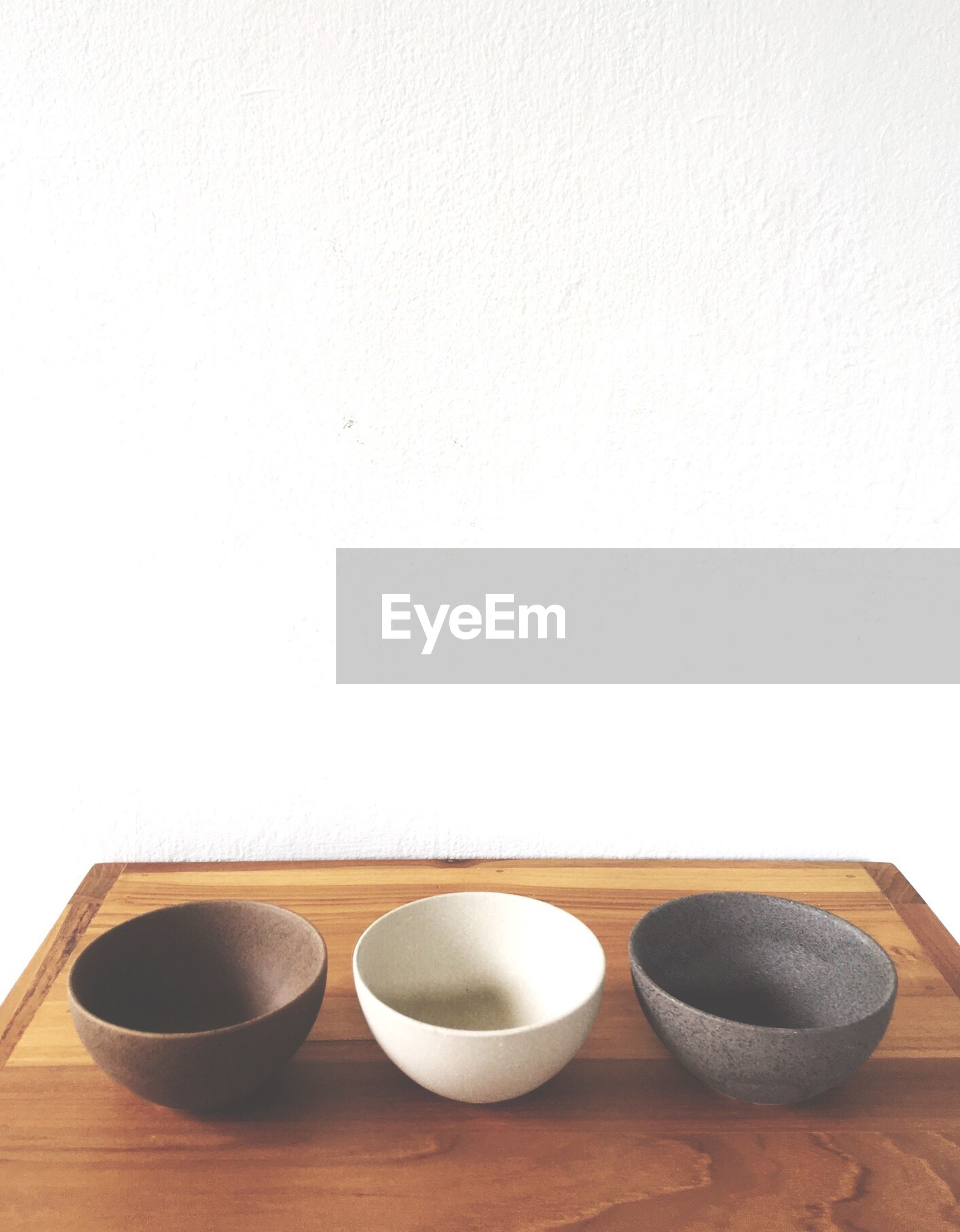 Close-up of bowls on wooden table against wall