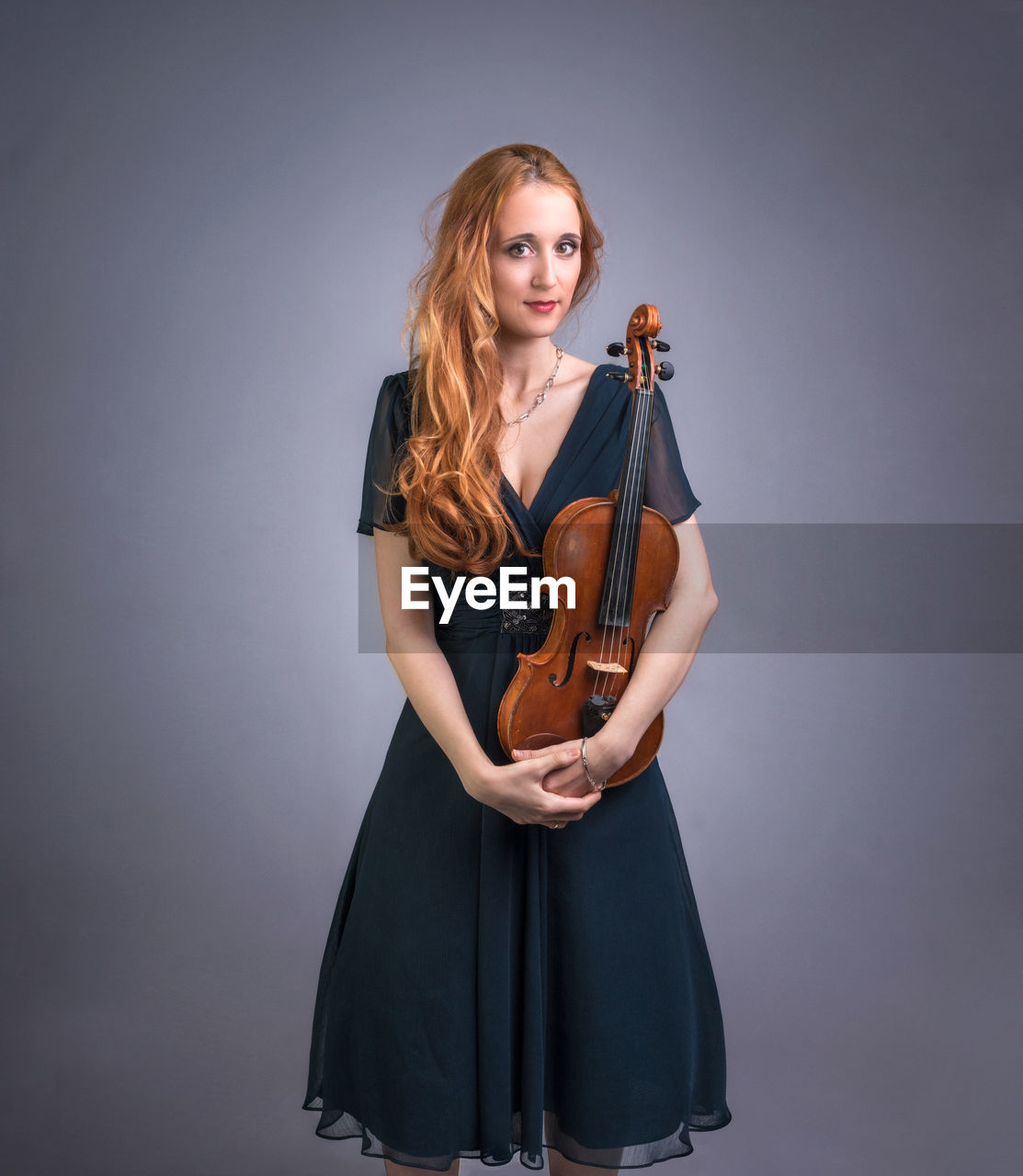 Portrait Of Beautiful Woman Holding Violin Against Gray Background