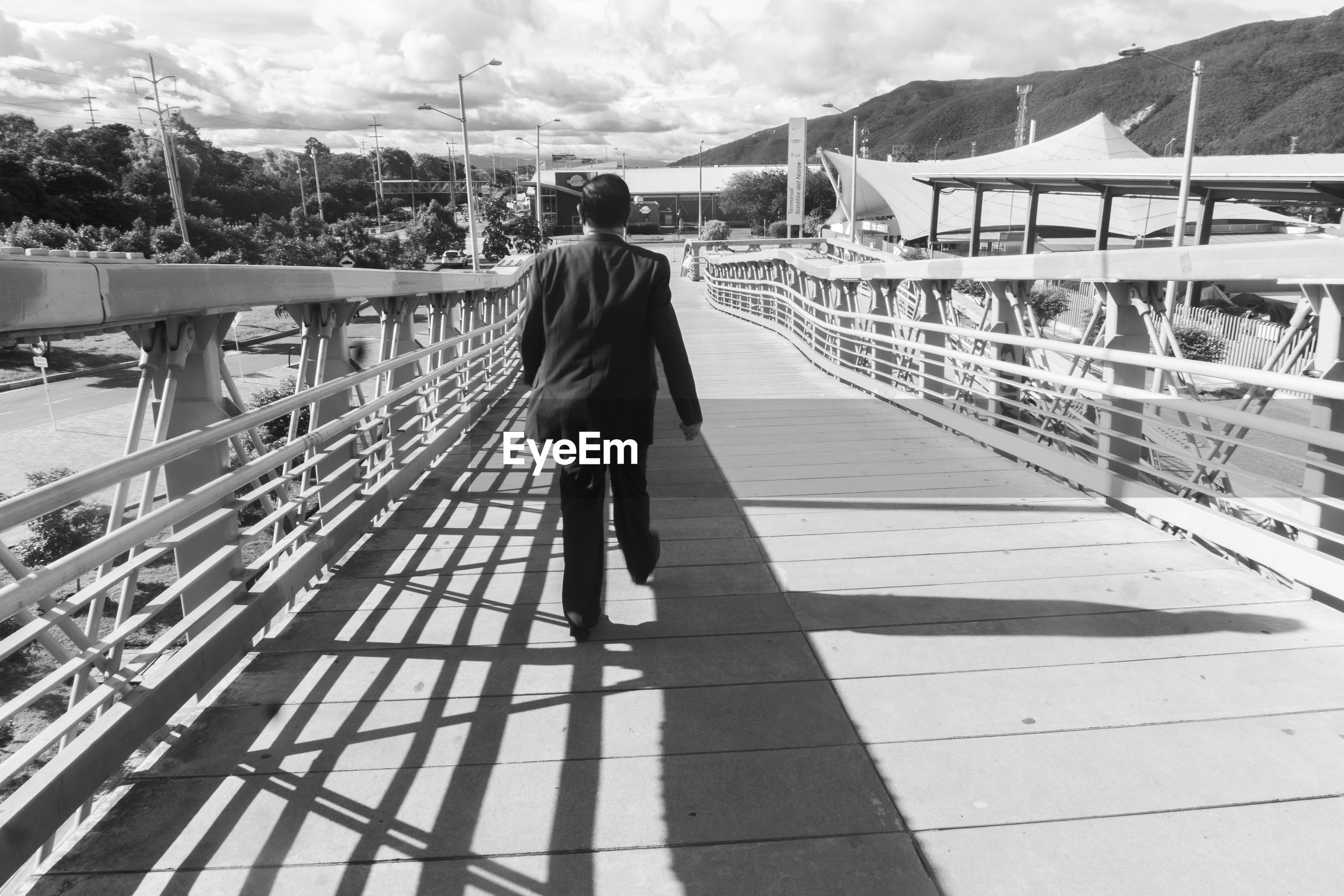 REAR VIEW OF MAN STANDING ON FOOTBRIDGE AGAINST SKY