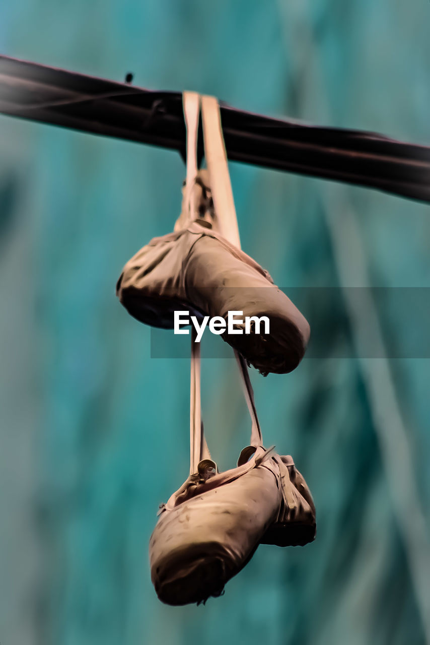 Low angle view of ballet shoes hanging on metal
