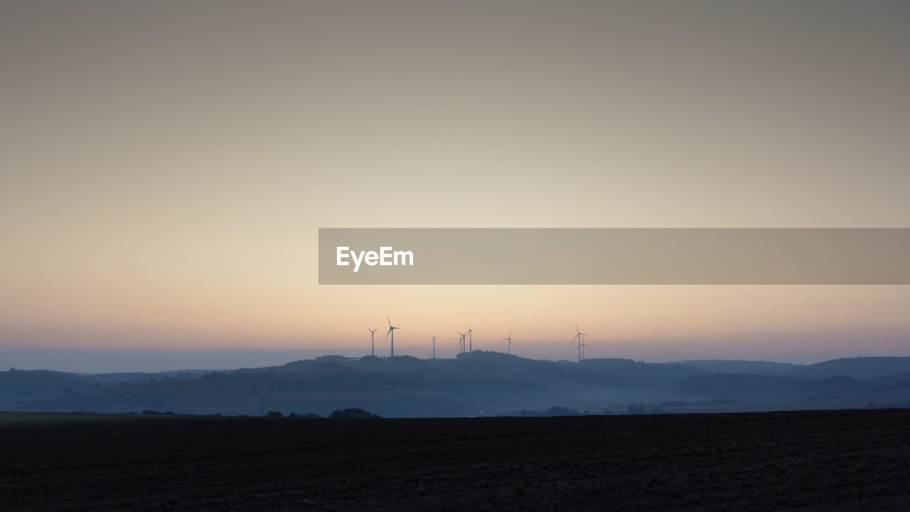 sky, sunset, scenics - nature, environment, beauty in nature, land, landscape, tranquil scene, orange color, copy space, silhouette, tranquility, fuel and power generation, nature, field, no people, mountain, non-urban scene, idyllic, outdoors