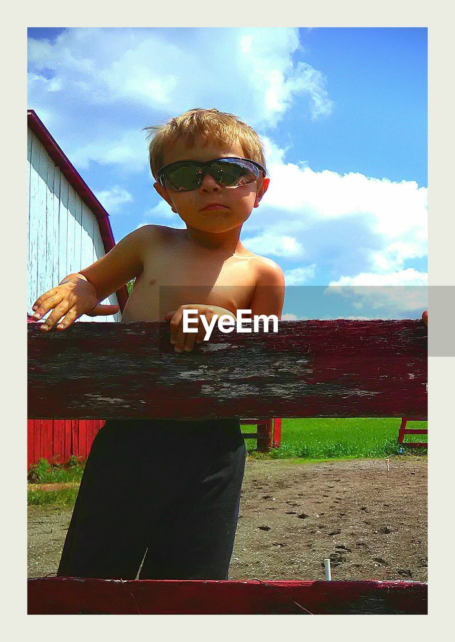 sunglasses, childhood, sky, boys, one person, real people, day, front view, outdoors, leisure activity, standing, cloud - sky, elementary age, one boy only, cute, sunlight, grass, looking at camera, portrait, children only, people
