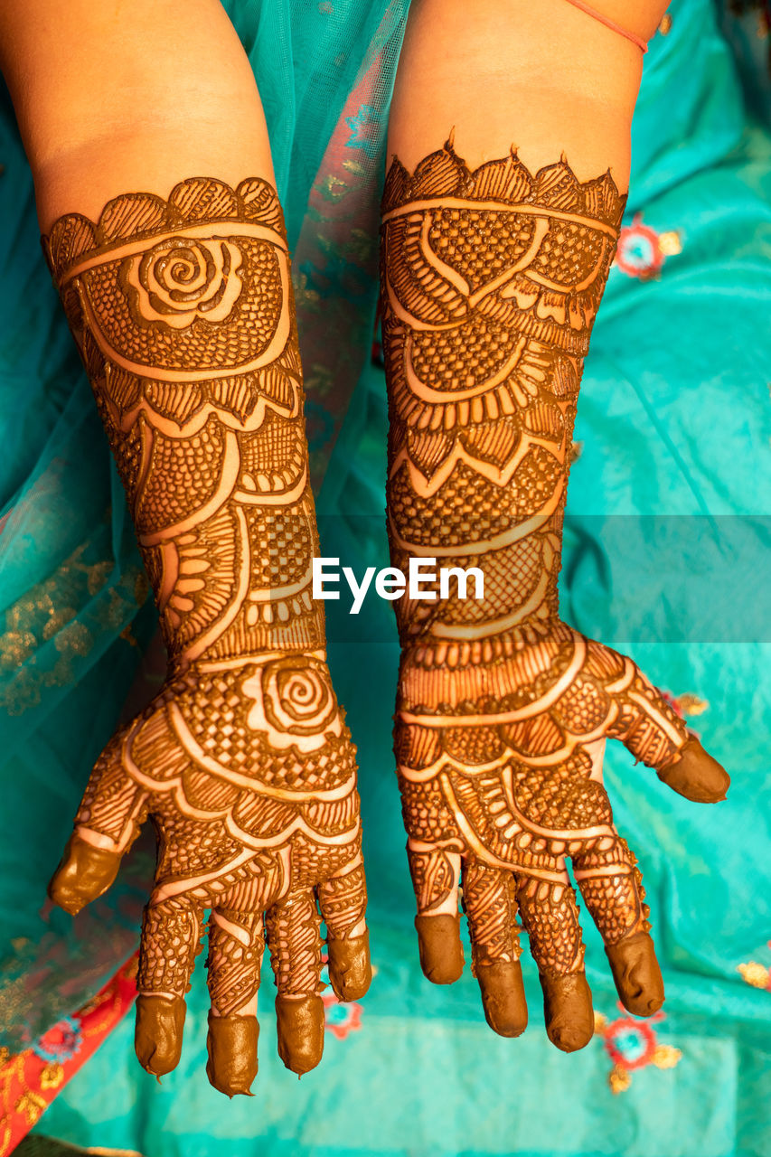 Midsection of bride showing henna tattoo