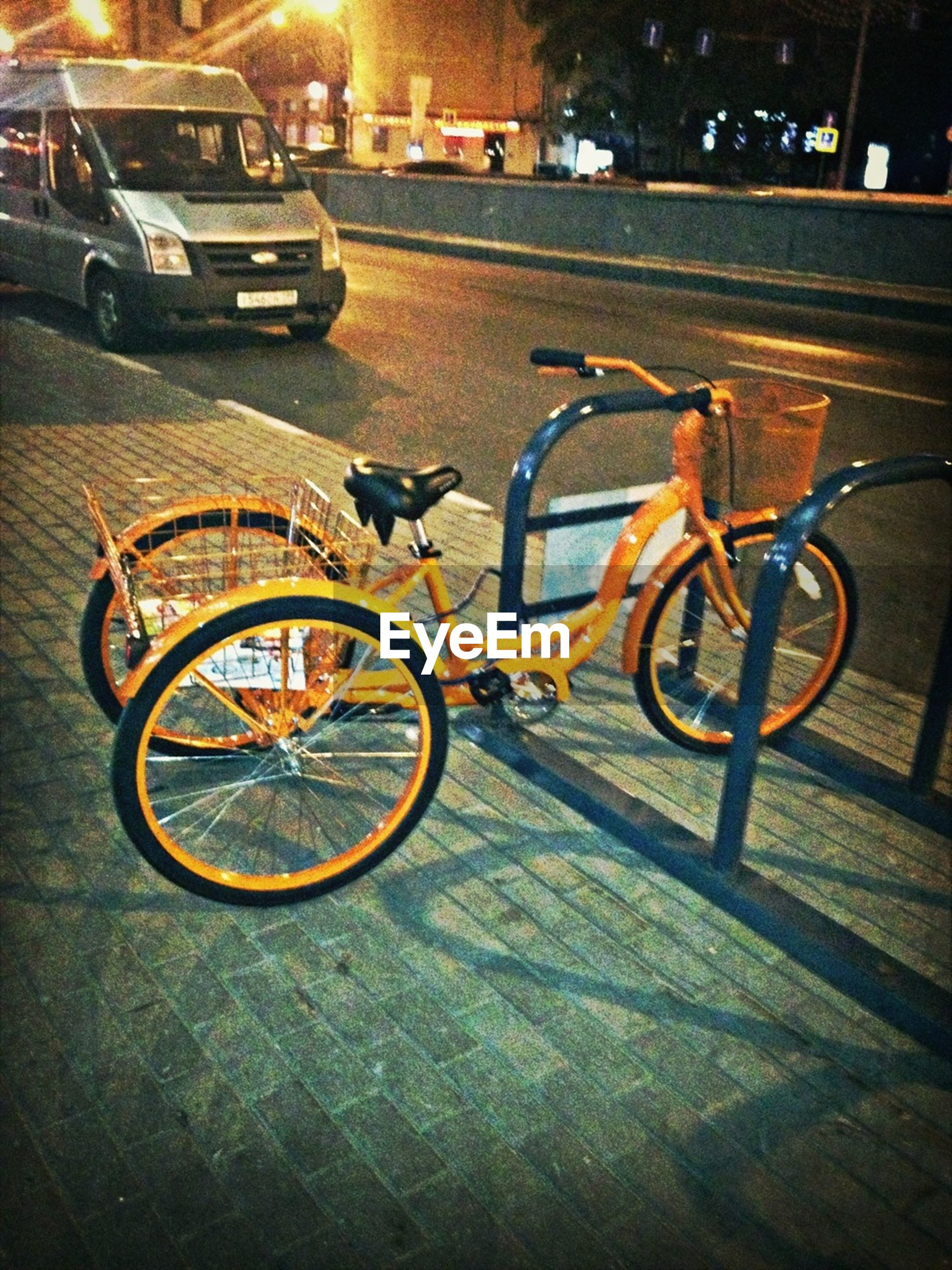 bicycle, transportation, land vehicle, street, mode of transport, stationary, parking, sidewalk, cobblestone, parked, road, building exterior, night, outdoors, car, no people, built structure, paving stone, city, footpath