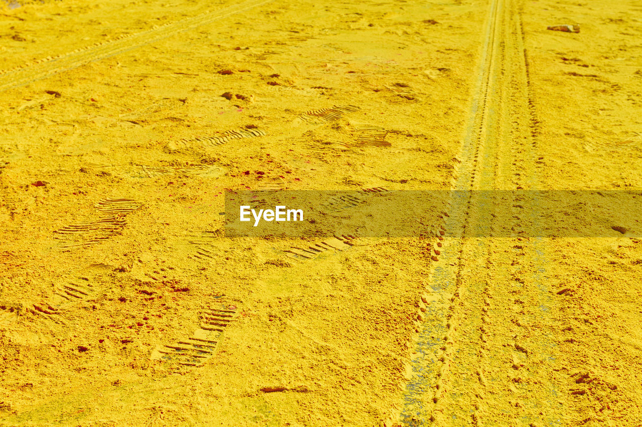 yellow, no people, day, tire track, land, nature, high angle view, full frame, dirt, pattern, outdoors, print, field, backgrounds, road, sunlight, track, landscape, sand, direction, mud