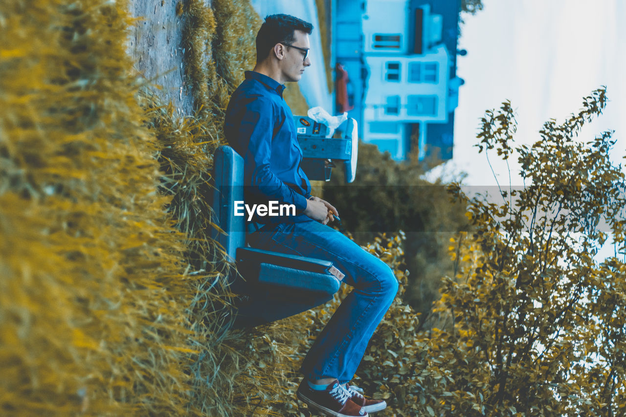 Tilt Image Of Man Sitting On Bench