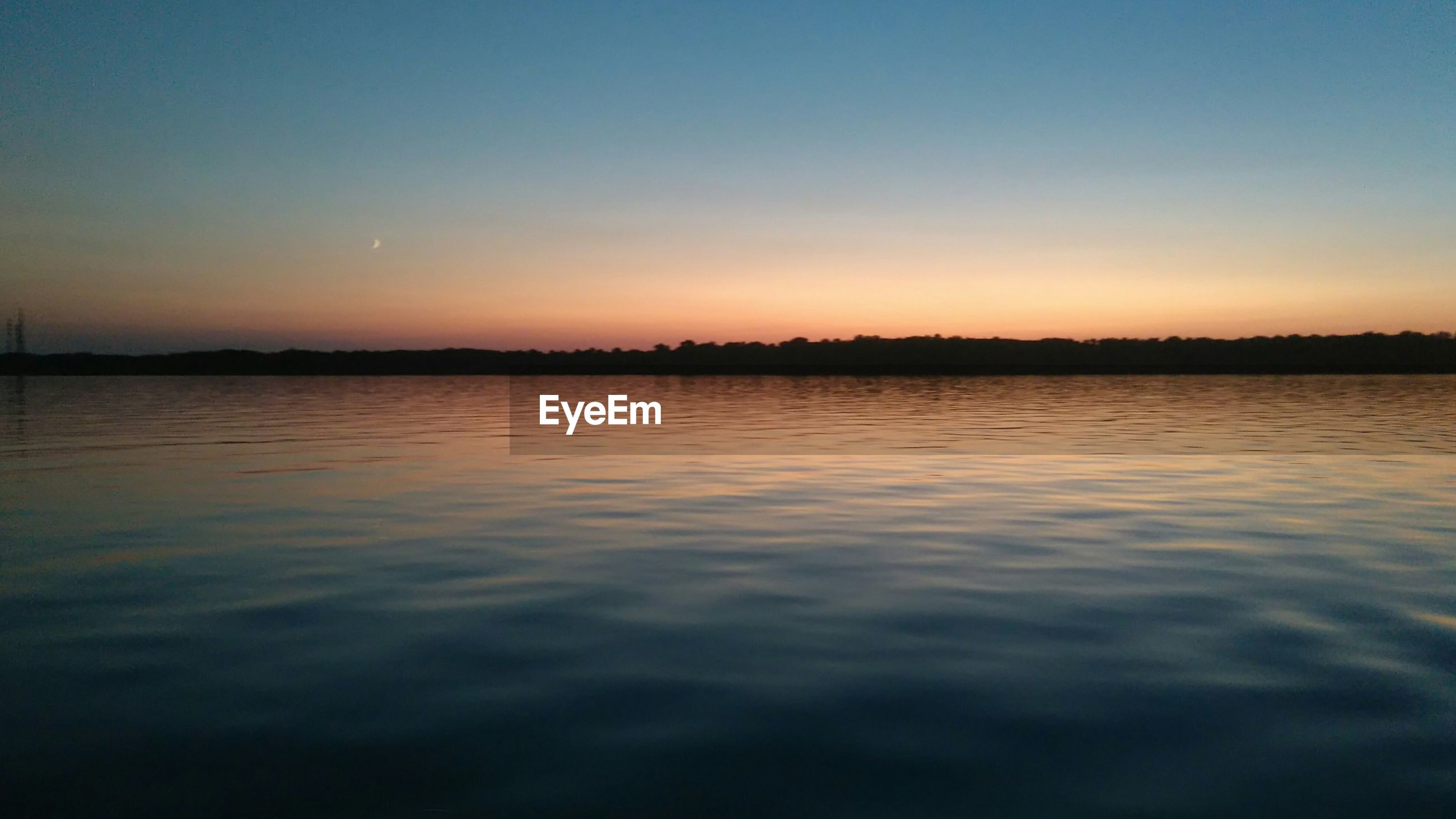 SCENIC VIEW OF CALM LAKE AT SUNSET