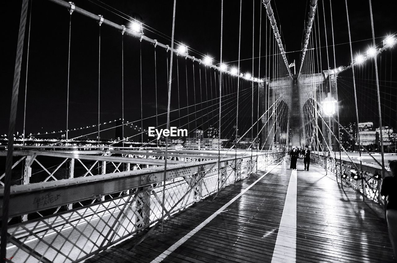 illuminated, bridge, transportation, architecture, night, built structure, bridge - man made structure, connection, engineering, motion, suspension bridge, city, real people, sky, nature, travel destinations, travel, water, outdoors, blurred motion