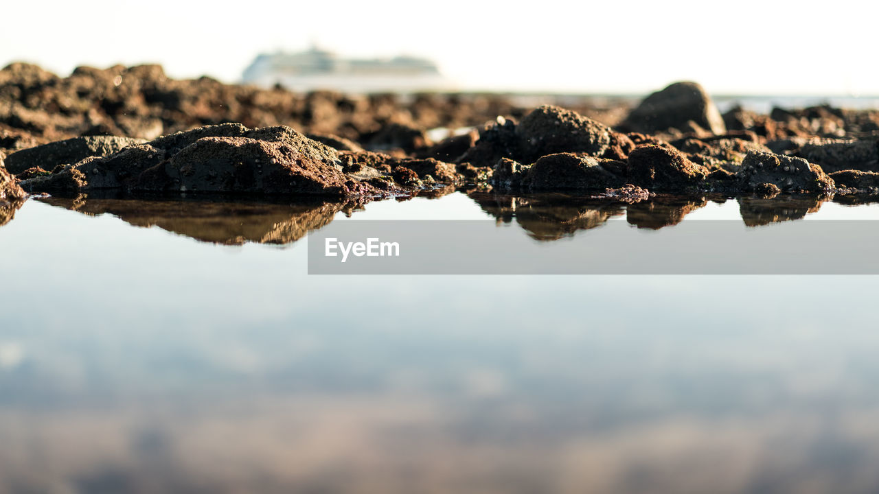 sky, no people, selective focus, water, nature, tranquility, rock, solid, day, rock - object, beauty in nature, scenics - nature, close-up, outdoors, tranquil scene, reflection, waterfront, sea, surface level